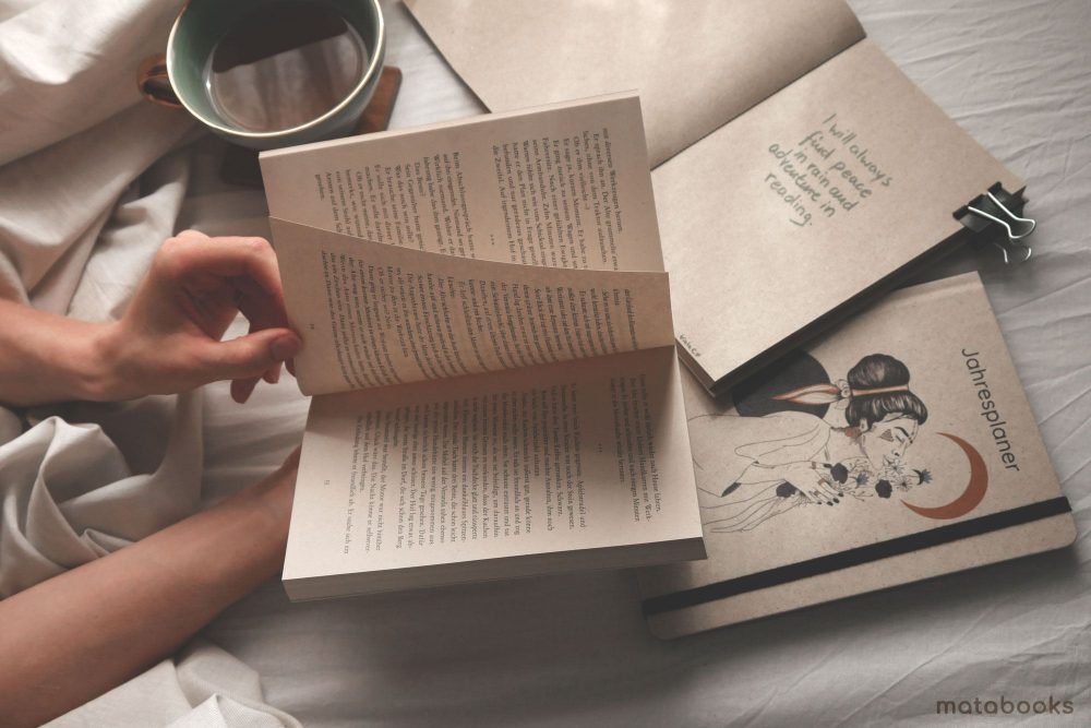 Aufgeschlagener Roman von Matabooks auf Bett