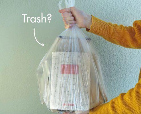 Hand hält Mülltüte mit Matabooks Notizbüchern aus Graspapier