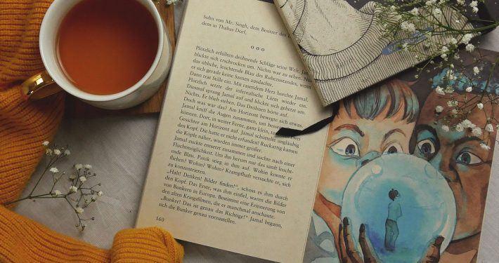Buch liegt aufgeschlagen auf einem Tisch mit einer Tasse Tee